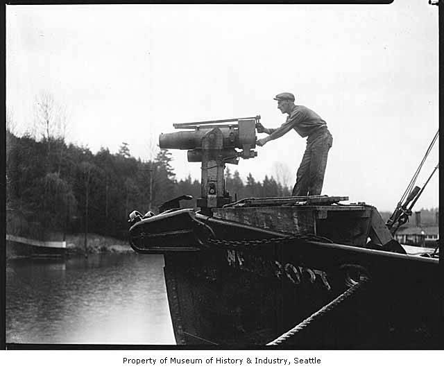 A young man in Bellevue's Meydenbauer Bay demonstrates a harpoon gun used to hunt whales ca. 1925.