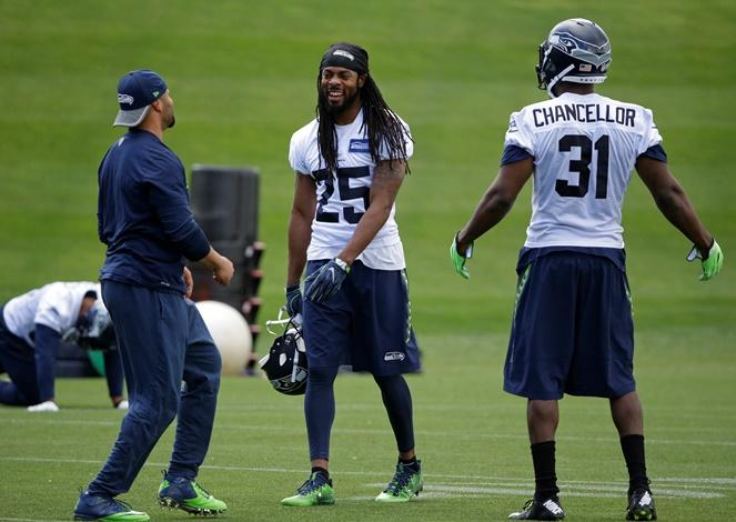Seahawks cornerback Richard Sherman (25) is all smiles as he and strong safety Kam Chancellor (31) talk with defensive coordinator Kris Richard left, during practice, Friday, June 9, 2017, in Renton.