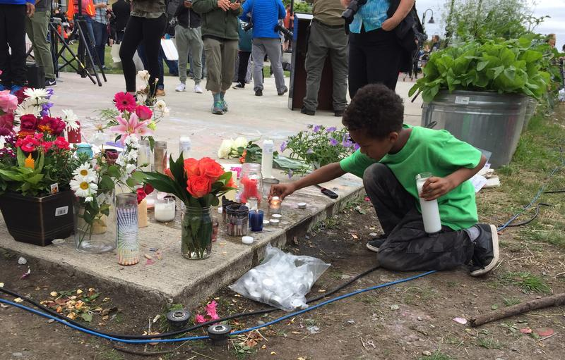 A boy lights a candle at a June 20, 2017, vigil for Charleena Lyles