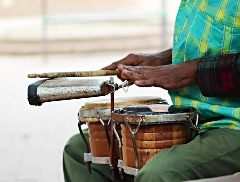 Cuban street musician plays bongos and cowbell