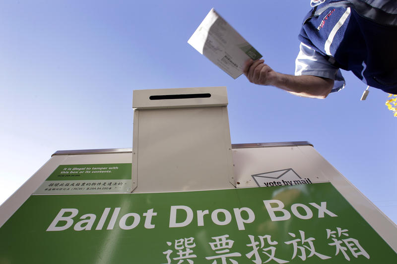 A voter drops off his ballot at a King County Elections drop box.