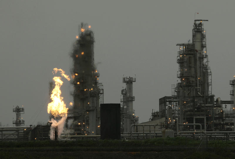 In this April 2, 2010, file photo, a Tesoro Corp. refinery, including a gas flare flame that is part of normal plant operations, is shown in Anacortes, Wash. after a fatal overnight fire and explosion.
