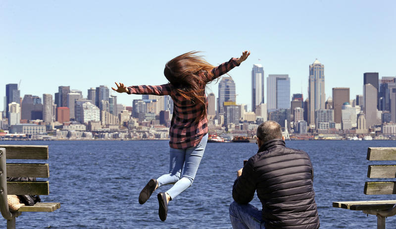 Mariel Toledo leaps for a photo taken by her friend Chi Nguyen in view of downtown Seattle