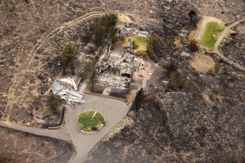 In this July 24, 2014 aerial file photo, the remains of structures that were destroyed by wildfires near Pateros, Wash. are shown. The fire was part of the Carlton Complex, the largest wildfire in state history.