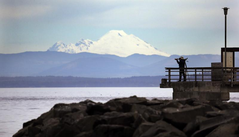 A photographer looks out over the Puget Sound and Mount Baker, some 70 miles distant, Friday, March 13, 2015, at the marina in Edmonds, Wash.