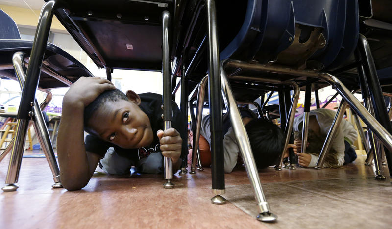 In this file photo from Oct. 2016, a student covers his head under a table at Lowell Elementary School in Seattle during a statewide earthquake drill. Now, communities are going beyond drop and cover by learning how to prioritize emergency communications.