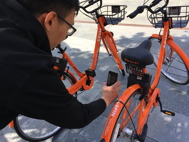 Spin CEO Derrick Ko demonstrates how to unlock his company's stationless bicycles. Spin launched in Seattle Monday.
