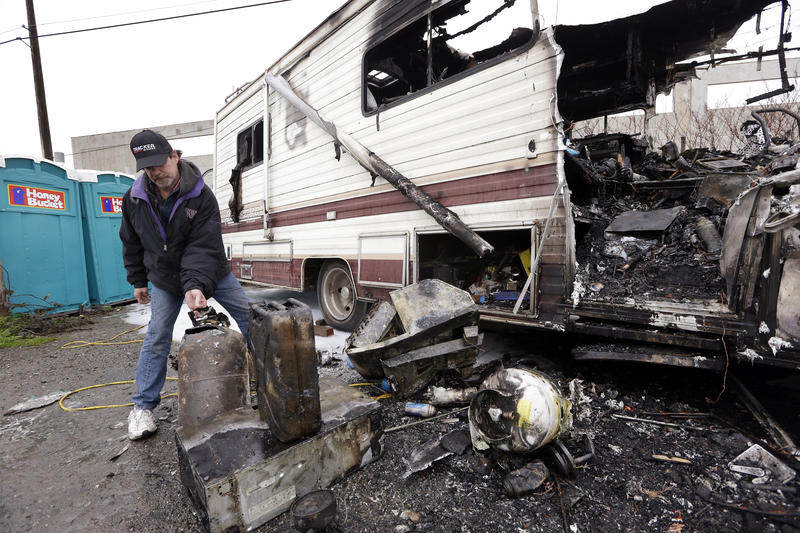 Clayton Lewis looks through the remains of an RV that was destroyed in an accidental fire in a Seattle homeless encampment for RVs and cars in 2016.