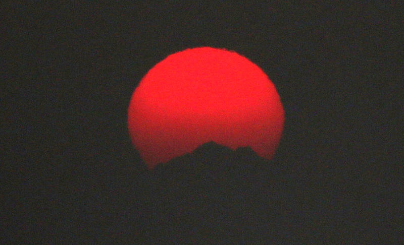 The sun sets over the Olympic Mountains, made a brilliant red because of smoke from fires raging in British Columbia that swept down into the Puget Sound region, Wednesday, Aug. 2, 2017, in Seattle.