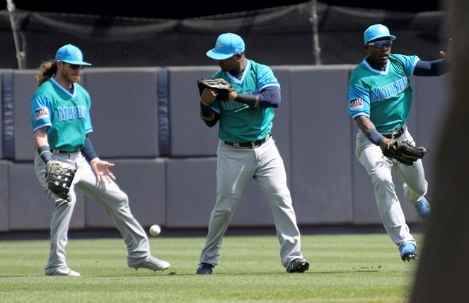Mariners left fielder Ben Gamel, left, shortstop Jean Segura and center fielder Guillermo Heredia, right, converge on a single hit during the first inning of a game against the Yankees, Sunday, Aug. 27, 2017, at Yankee Stadium in New York.