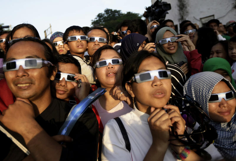 In this March 9, 2016 file photo, people wearing protective glasses look up at the sun to watch a solar eclipse in Jakarta, Indonesia.