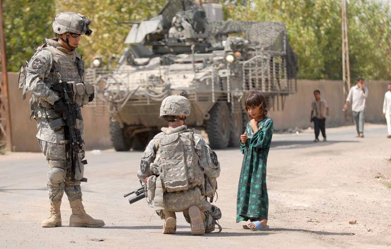 Two soldiers from Joint Base Lewis-McChord talk with a young Iraqi girl