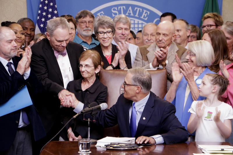 Gov. Jay Inslee shakes hands with Ross Hunter, the new head of the Department of Children, Youth and Families shortly after Inslee signed the bill creating the new agency on July 6.