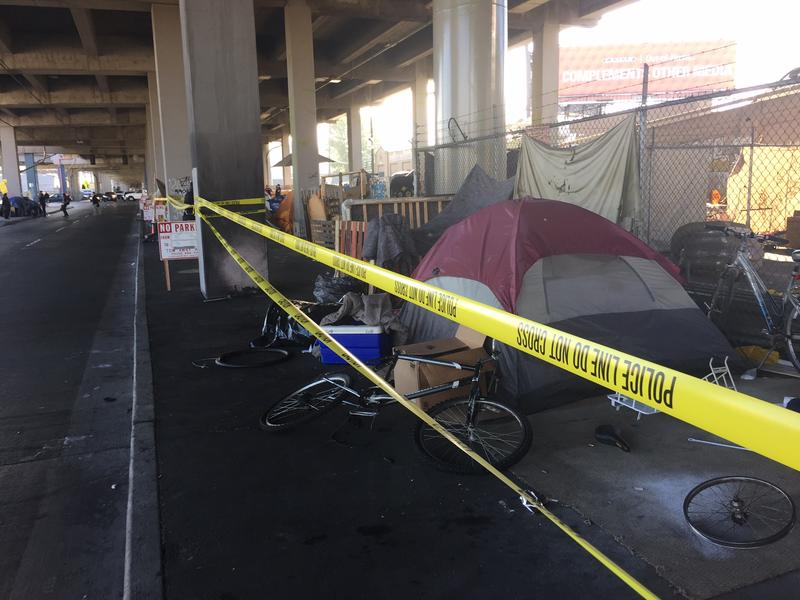 City workers put up tape designating the homeless encampment slated to be cleared.