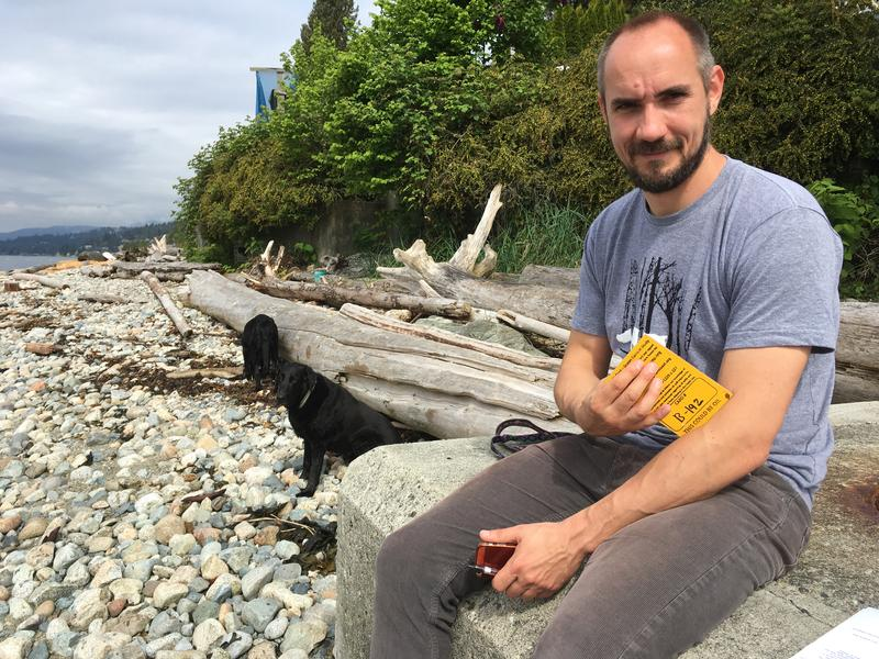 Ross Dixon, Program Manager with the Raincoast Conservation Foundation, holds a drift card he found on this beach in Dundarave, north Vancouver, BC.