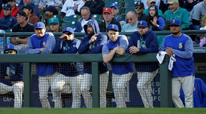 Mariners players stand at the dugout rail during the ninth inning of a baseball game against the Cleveland Indians, Sunday, Sept. 24, 2017, in Seattle. The Mariners were eliminated from post-season play as the Indians won 4-2.