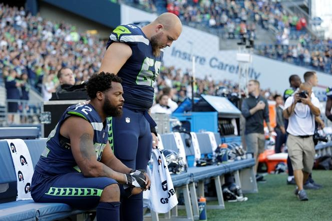 Seahawks defensive end Michael Bennett, left, sits during the singing of the national anthem as center Justin Britt, right, stands next to him before an NFL football preseason game against the Kansas City Chiefs, Friday, Aug. 25, 2017, in Seattle.