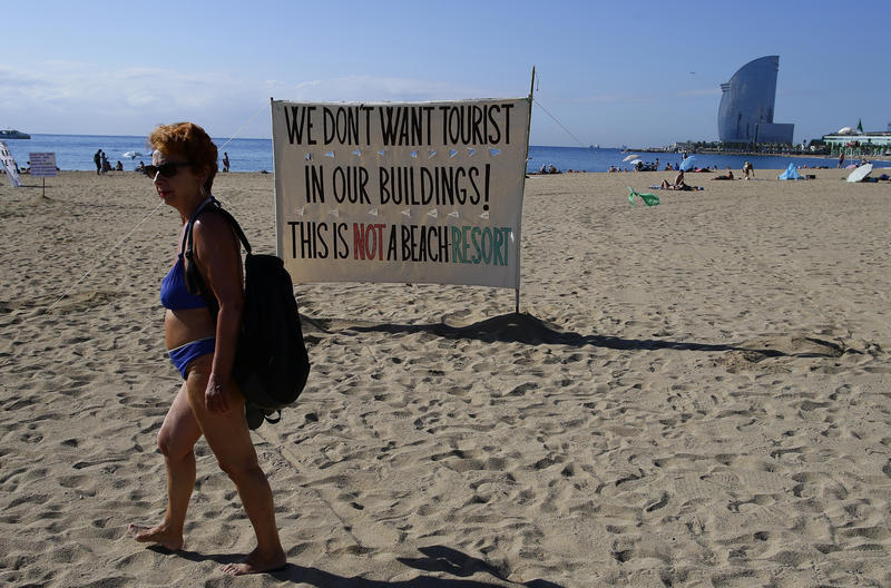 A woman walks past a banner during a protest against tourism in Barcelona, Spain, this past August. Residents say the influx of visitors has hiked rents and caused a spike in rowdy behavior by party-seeking foreigners.