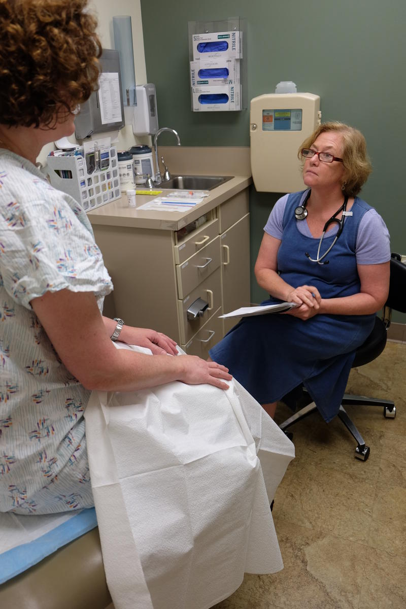 A nurse practitioner listens to a patient.