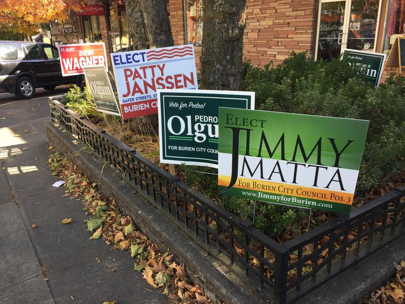 A streetcorner cluttered with campaign signs in downtown Burien