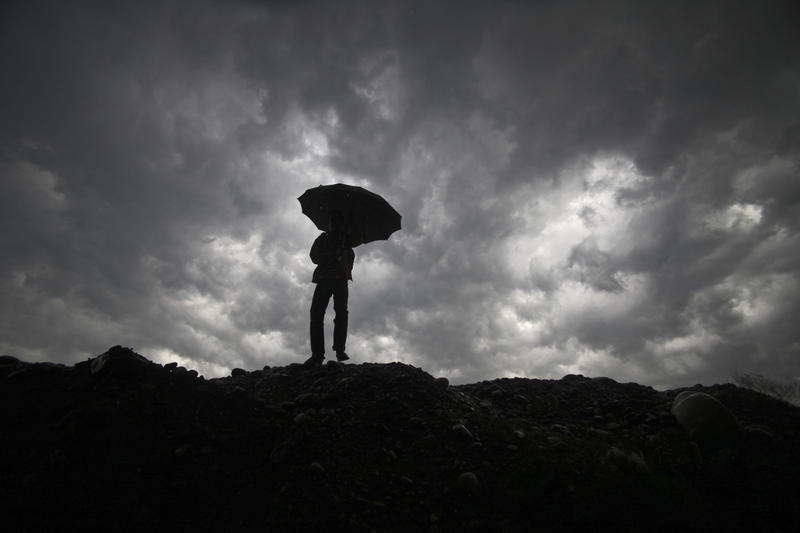 In this file photo from 2011, a boy walks with an umbrella to protect himself from the rain, as dark clouds hover over him in Jammu, India. If Earth overheats, can it be artificially cooled? Should the effort begin now? Who would decide?