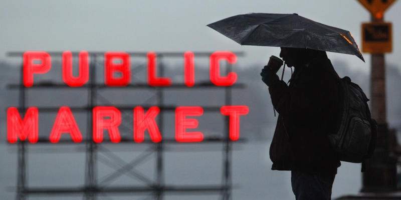 A pedestrian sips coffee under the protection of an umbrella in a steady rain and in view of the Pike Place Market Tuesday, Nov. 22, 2011, in Seattle.