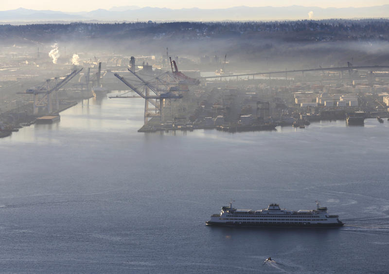 A Washington state ferry heads for downtown Seattle past the Port of Seattle on a misty morning as viewed from the roof of the Space Needle, Friday, Jan. 6, 2017.