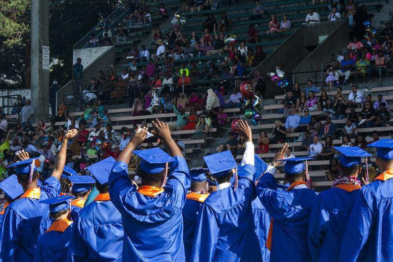 Rainier Beach High School seniors wave to the crowd watching their graduation ceremony in the stands of Memorial Stadium at Seattle Center in June 10, 2015. About half of the students at the Southeast Seattle school are black or African-American.