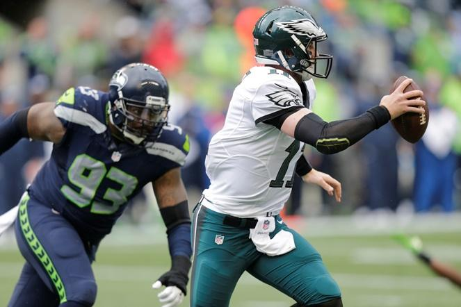 Philadelphia Eagles quarterback Carson Wentz, right, scrambles away from Seattle Seahawks defensive tackle Tony McDaniel (93) in the first half of a game, Sunday, Nov. 20, 2016, in Seattle.