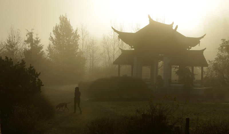 A woman walks her dog through morning fog near the Fuzhou Ting Pavilion at the Chinese Reconciliation Park in Tacoma, Wash. on Dec. 7th, 2017.
