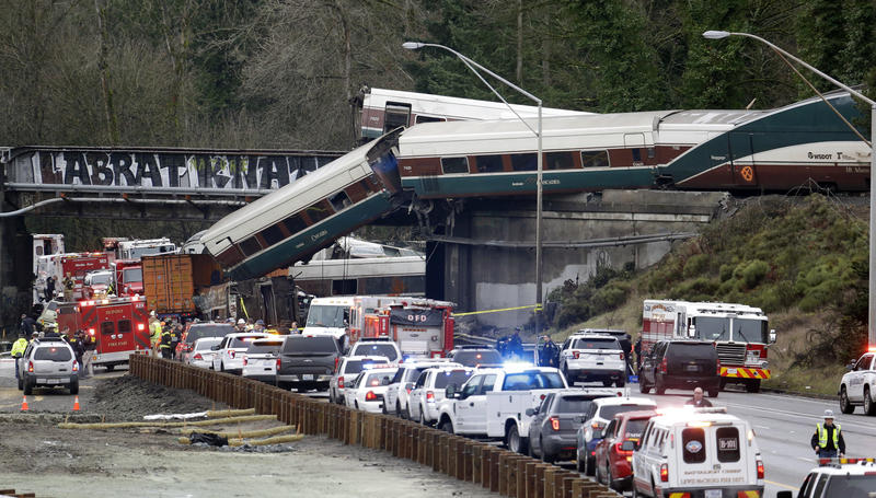 Cars from an Amtrak train lay spilled onto Interstate 5 below as some remain on the tracks above Monday, Dec. 18, 2017, in DuPont, Wash.