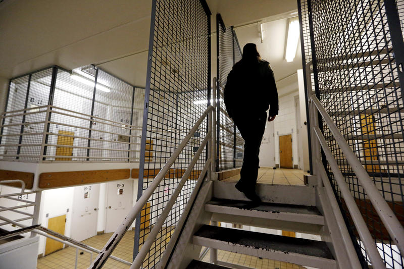 A Pierce County corrections deputy walks the psychiatric unit of the Pierce County Jail on Oct. 15, 2014