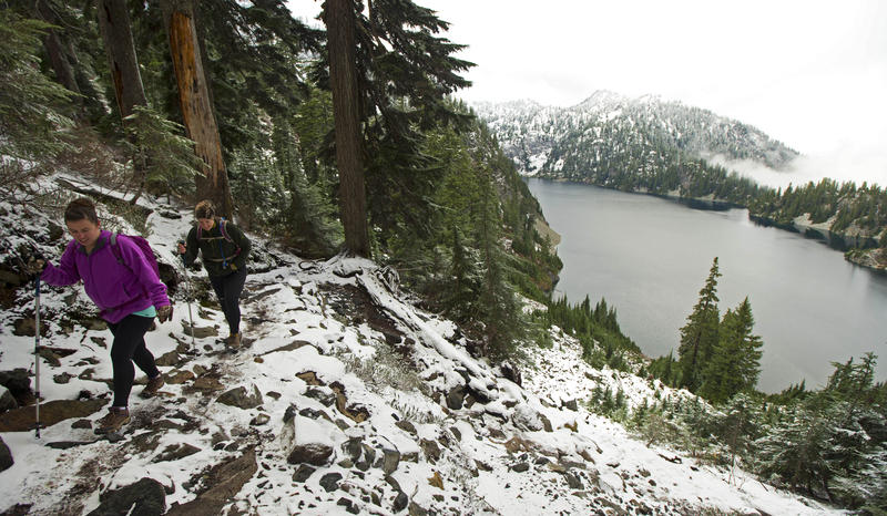 In this Nov. 3, 2015, file photo, Kasee Palmer, left, and Summer Sturhan, both of Olympia, Wash., hike on Snow Lake Trail above Snoqualmie Pass in Washington state, as some of the first snow of the season fell in the area.
