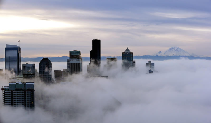 Downtown buildings rise above a low-level morning fog as Mount Rainier is seen some 80 miles distant Friday, Jan. 9, 2015 in Seattle. Winter temperature inversions often come with this kind of fog.