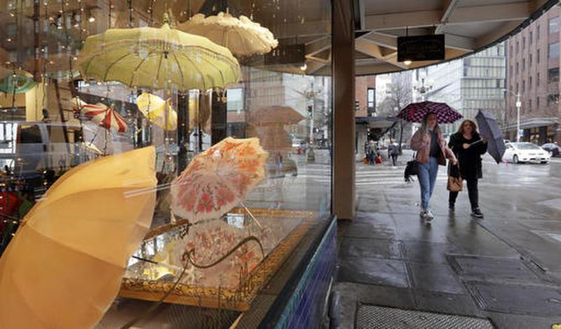 In This Jan. 18, 2017 file photo pedestrians under umbrellas pass a vintage umbrella shop in downtown Seattle.