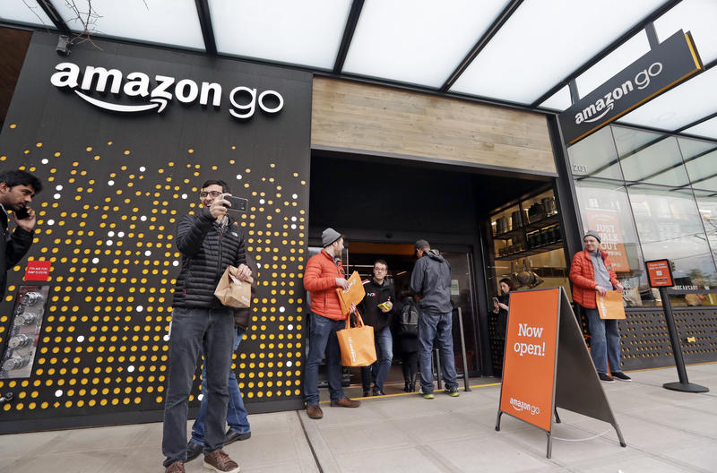 People stand outside an Amazon Go store Monday, Jan. 22, 2018, in Seattle.