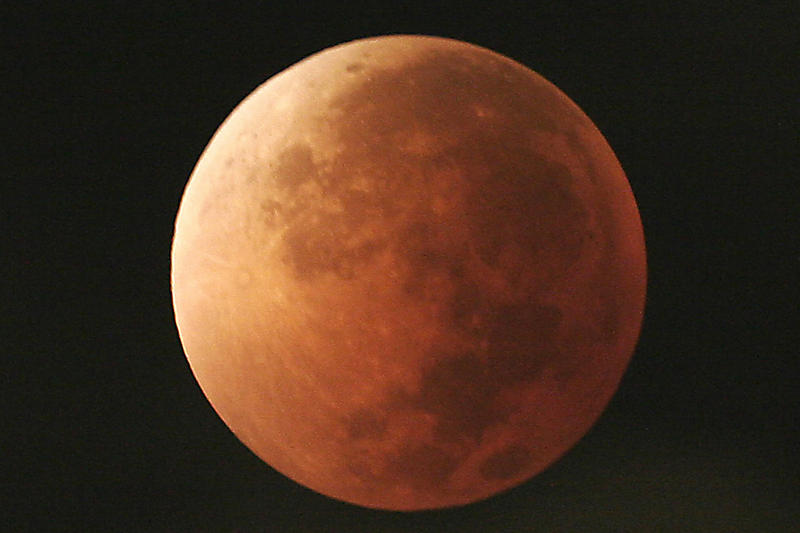 In this Aug. 28, 2007, file photo, the moon takes on different orange tones during a lunar eclipse seen from Mexico City.