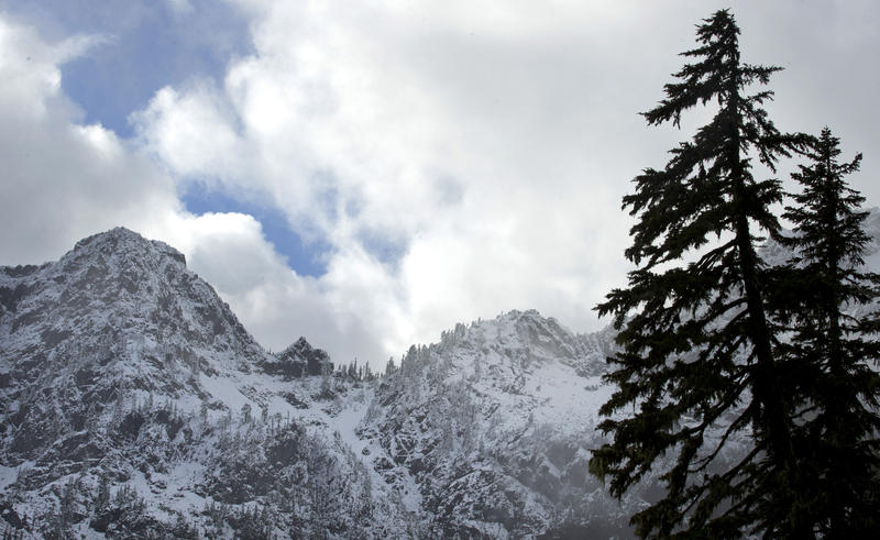 In this Nov. 3, 2015, file photo, snow covers mountains in this view from the Snow Lake hiking trail above Snoqualmie Pass in Washington state.