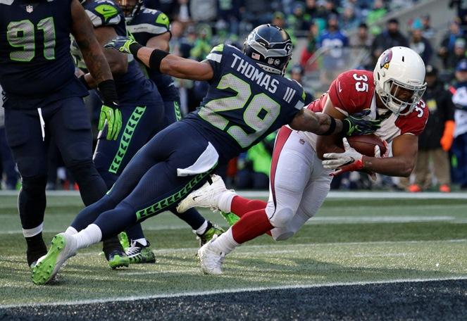 Arizona Cardinals running back Elijhaa Penny dives past Seahawks free safety Earl Thomas to score a touchdown in the first half of the final regular season game, Sunday, Dec. 31, 2017, in Seattle.