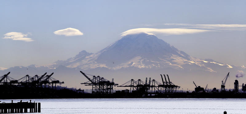 A lenticular cloud, that often signals rainy weather ahead, forms a cap atop Mount Rainier behind cranes that service container ships along the Duwamish River, Tuesday, Feb. 13, 2018, in Seattle.