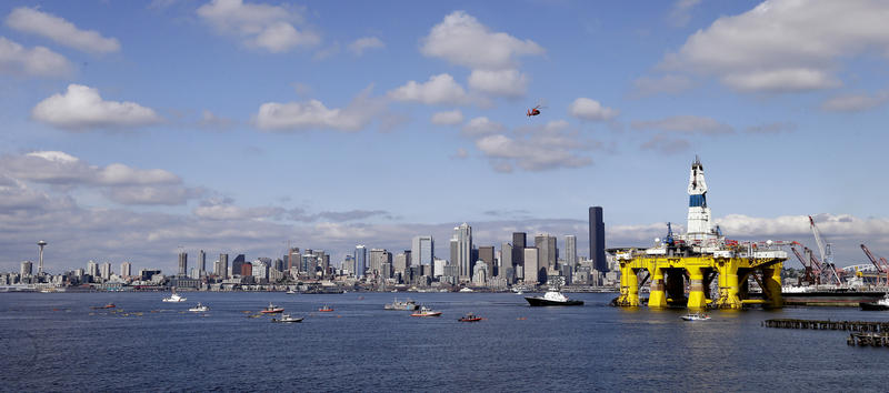 A U.S. Coast Guard helicopter flies overhead and a small flotilla of protesters in kayaks paddles behind as the oil drilling rig Polar Pioneer is towed toward a dock Thursday, May 14, 2015, in Elliott Bay in Seattle.