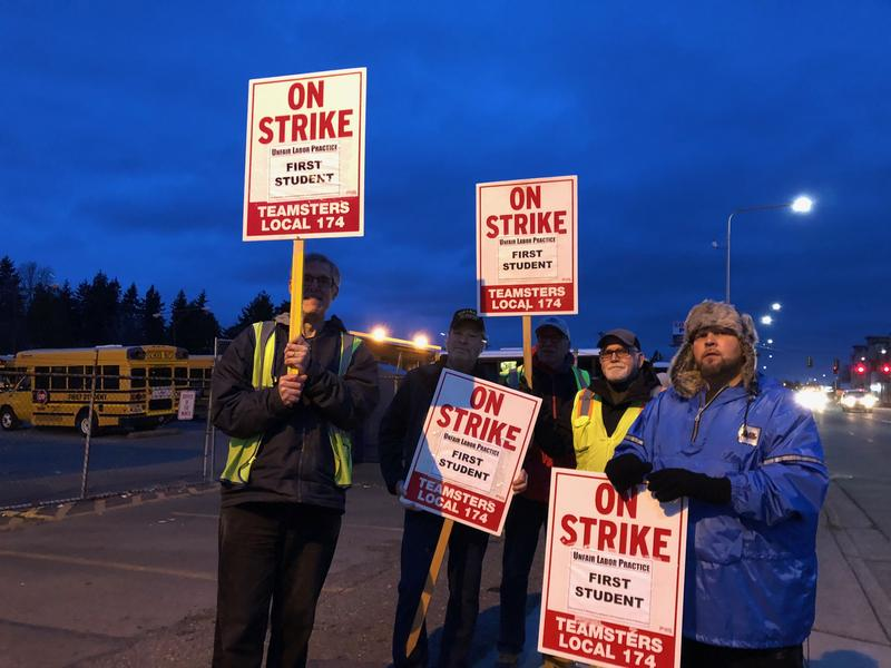 Seattle school bus drivers hold signs Thursday morning on Lake City Way. They are on strike over health and retirement benefits.