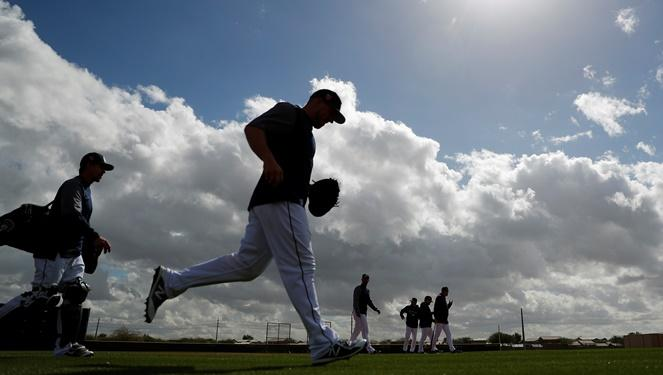 Seattle Mariners catchers run onto the field during a baseball spring training workout, Monday, Feb. 19, 2018, in Peoria, Ariz.