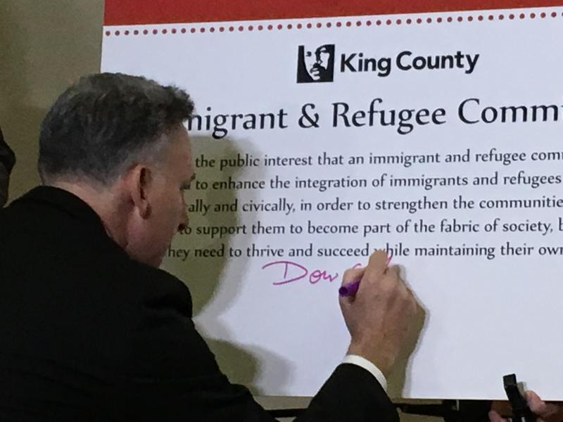 King County Executive Dow Constantine signs a law to create an Immigrant and Refugee Commission at a ceremony Tuesday.