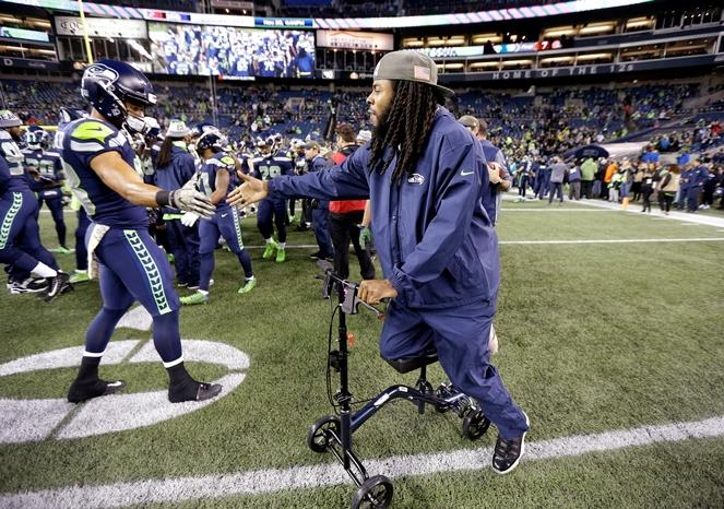 Seahawks cornerback Richard Sherman, right, greets D.J. Alexander as Sherman leans on a cart protecting his injured leg before an NFL football game against the Atlanta Falcons, Monday, Nov. 20, 2017, in Seattle.