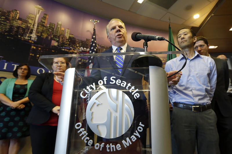 Seattle Mayor Ed Murray speaks at a news conference as his husband, Michael Shiosaki, right, stands nearby at City Hall Wednesday, June 14, 2017, in Seattle.