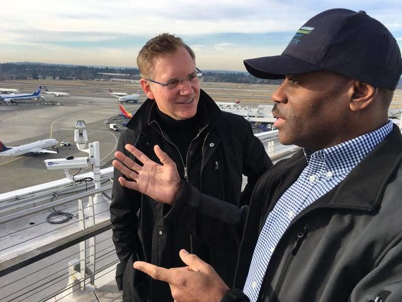 Lance Lyttle, Managing Director of the Port of Seattle's Aviation Division talks about the long-term future of the airport on its roof, with KNKX travel expert Matthew Brumley (left).