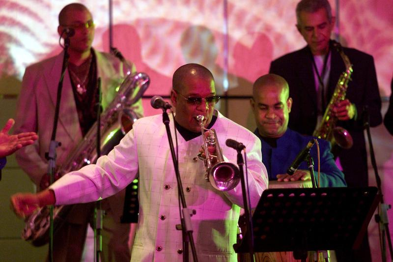 Jesus Alemany, center, band leader of Cubanismo, directs a performance while playing trumpet at the Singapore Arts Festival, Tuesday, June 11, 2002.
