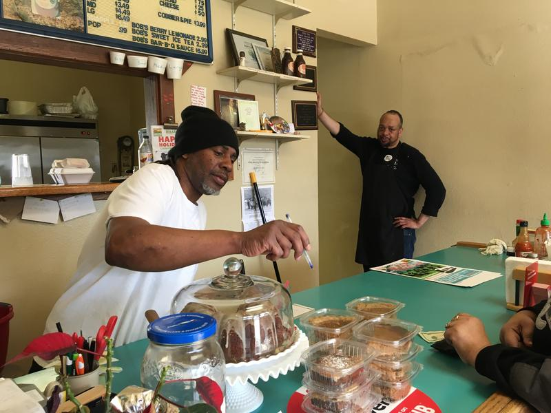 Jonathan Clark works the counter at Bob's Bar-B-Q Pit in Tacoma's Hilltop neighborhood, while his friend and colleague Paul Waller looks on