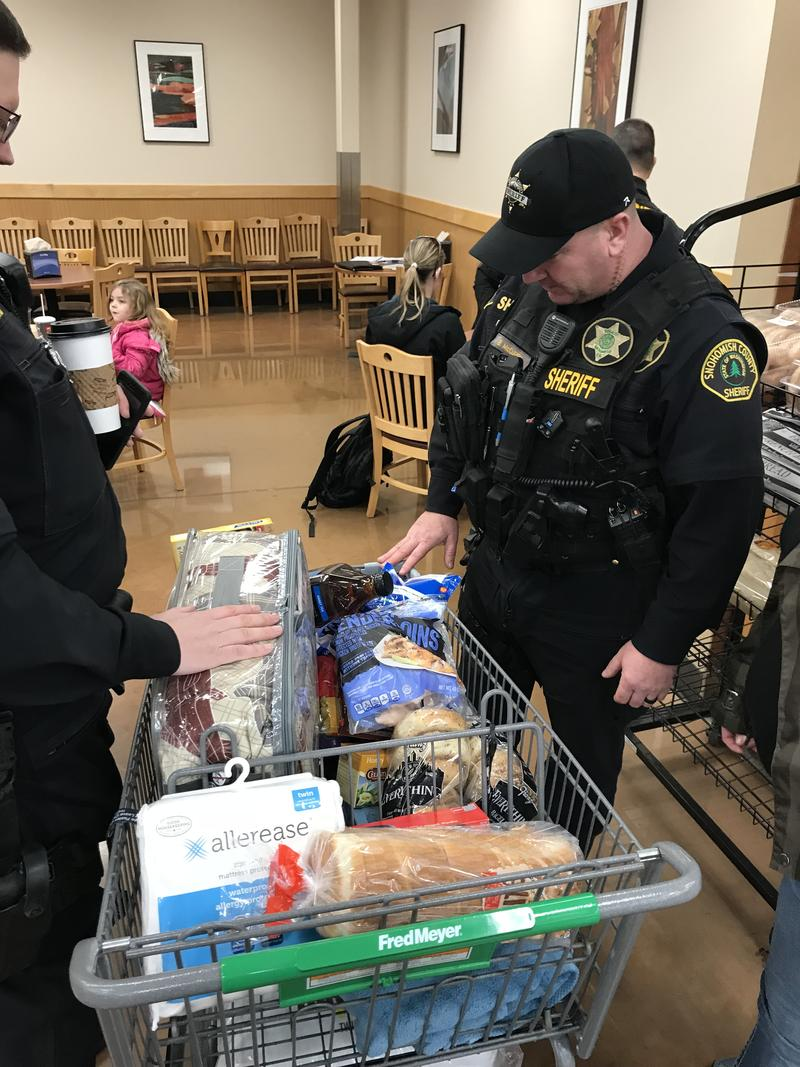 Sgt. Ian Huri (left) and Dep. Bud McCurry (right) look over a cart filled with food and bedding for Janelle
